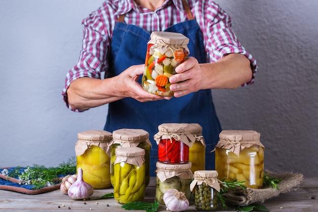 Starsza dojrzała kobieta trzyma w rękach słoik z domowej roboty konserwowane i sfermentowane jedzenie. odmiana warzyw marynowanych i marynowanych. gospodarstwo domowe, ekonomika domu, konserwacja zbiorów