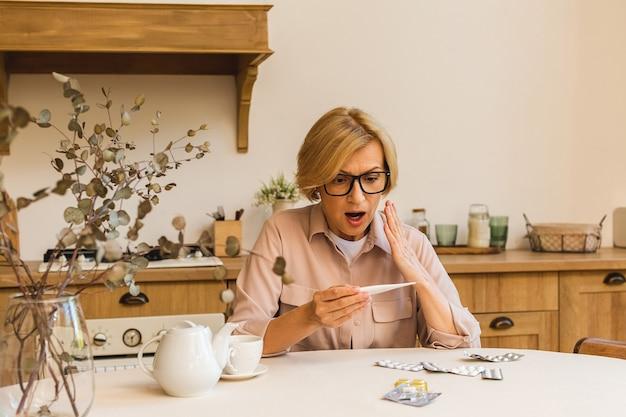 Starsza dojrzała kobieta z pigułkami mierzącymi temperaturę ciała termometrem medycznym w kuchni w domu. przeziębienie i grypa, koncepcja koronawirusa covid-19.