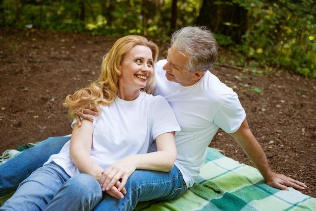 Starsza dorosła szczęśliwa para w parku przytulanie siedząc na kratę