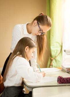 Starsza dziewczyna pomaga odrabiać lekcje młodszej siostrze