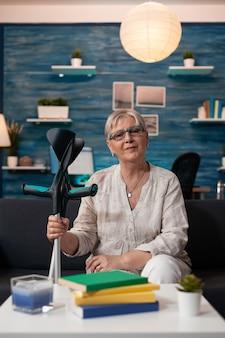 Starsza emerytowana kobieta siedzi na kanapie w salonie