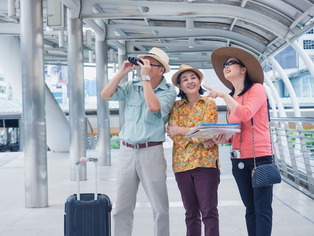 Starsza grupa spaceruje i rozmawia po mieście, starszy mężczyzna i kobieta podróżują w wakacje
