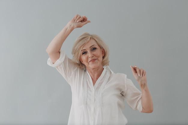 Starsza kaukaska starsza kobieta tańczy imprezę świętowanie na szarym tle starzy ludzie pozytywnie mnie...