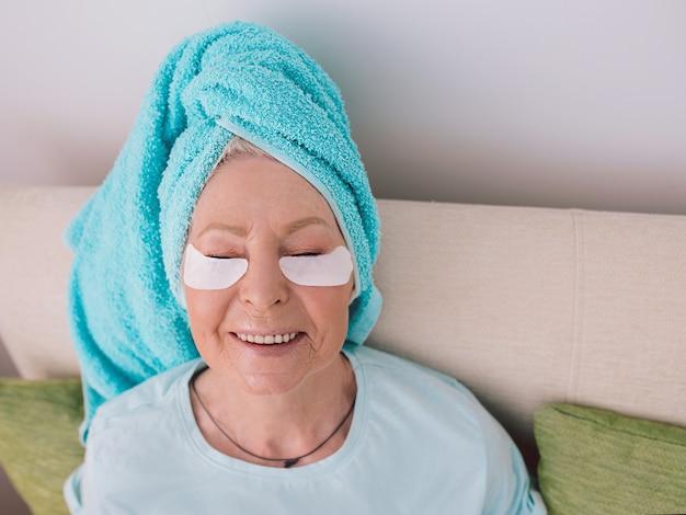 Starsza kaukaska stylowa kobieta leżąca w autokarze z niebieskim ręcznikiem miała kolagenowe opaski na oczy