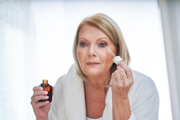 Starsza kobieta aplikująca serum do twarzy w łazience