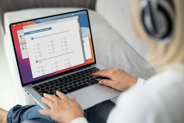 Starsza kobieta bierze lekcję online na swoim laptopie w domu