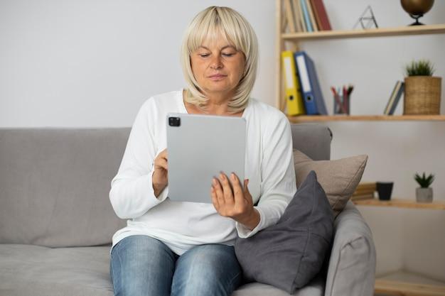 Starsza kobieta bierze lekcję online na swoim tablecie