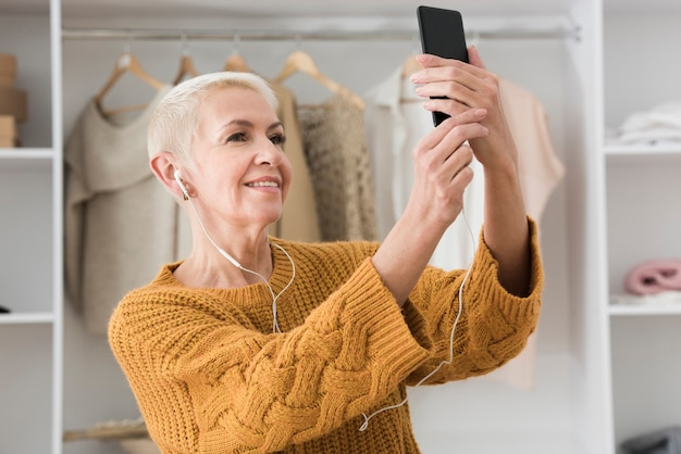 Starsza kobieta bierze selfie i słucha muzyka na hełmofonach
