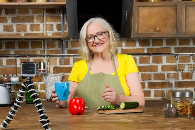Starsza kobieta blogger żywności nagrywania jej gotowania przez kamerę wideo