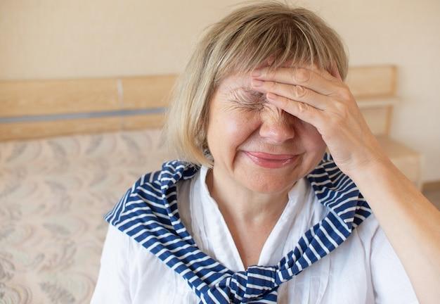 Starsza kobieta cielna ból głowy. pierwsze oznaki koronawirusa, wirusa oddechowego, choroby. pojęcie opieki zdrowotnej, stres, ból głowy, zawroty głowy, przemoc, migrena zdrowie psychiczne lęk emocjonalny