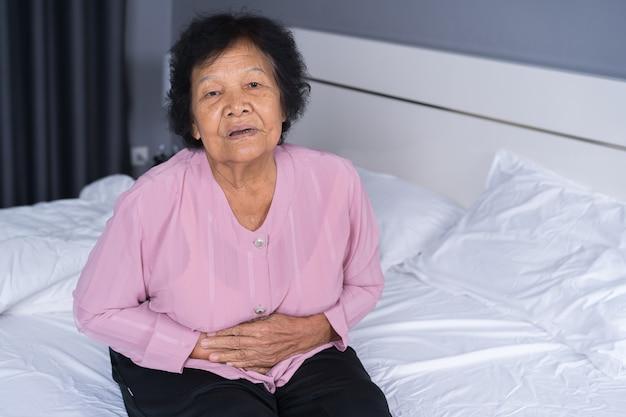 Starsza kobieta cierpi na ból brzucha na łóżku