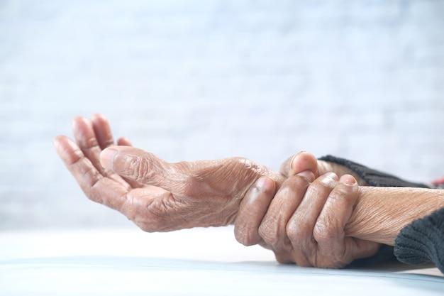 Starsza kobieta cierpi na ból na białym tle.