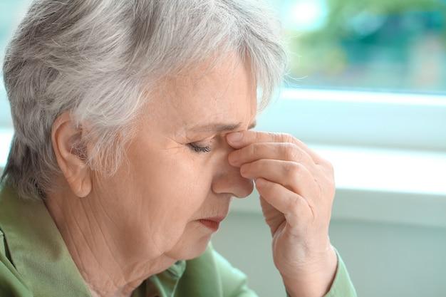 Starsza kobieta cierpiąca na ból głowy w domu