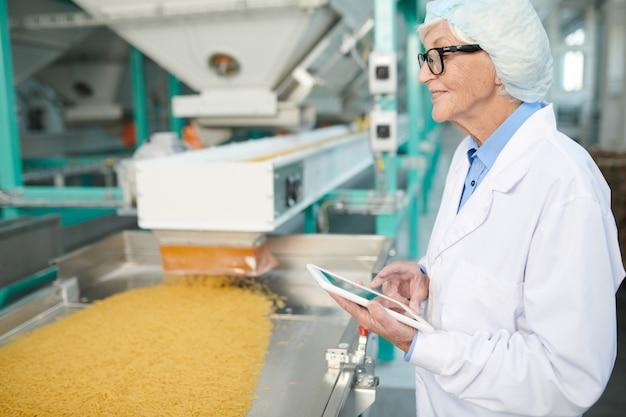 Starsza kobieta cieszy się pracę w fabryce