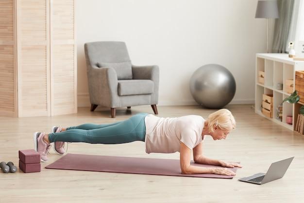 Starsza kobieta ćwiczenia na podłodze przed laptopem w salonie w domu