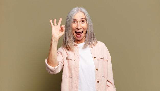 Starsza kobieta czuje się dobrze i jest zadowolona, uśmiechając się z szeroko otwartymi ustami, robiąc dobry znak ręką