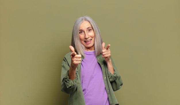 Starsza kobieta czuje się szczęśliwa, fajna, zadowolona, zrelaksowana i odnosząca sukcesy, wskazując na kamerę, wybierająca ciebie