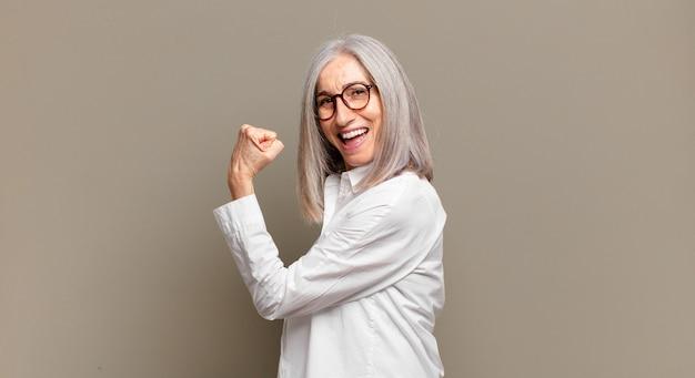 Starsza kobieta czuje się szczęśliwa, usatysfakcjonowana i potężna, wygina się i ma umięśnione bicepsy, wygląda dobrze po siłowni