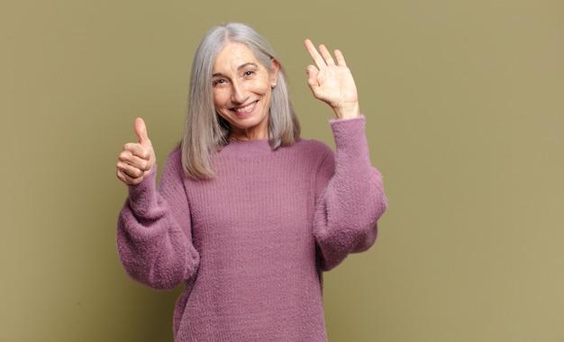 Starsza kobieta czuje się szczęśliwa, zdumiona, usatysfakcjonowana i zaskoczona, pokazując gesty w porządku i kciuki w górę, uśmiechając się