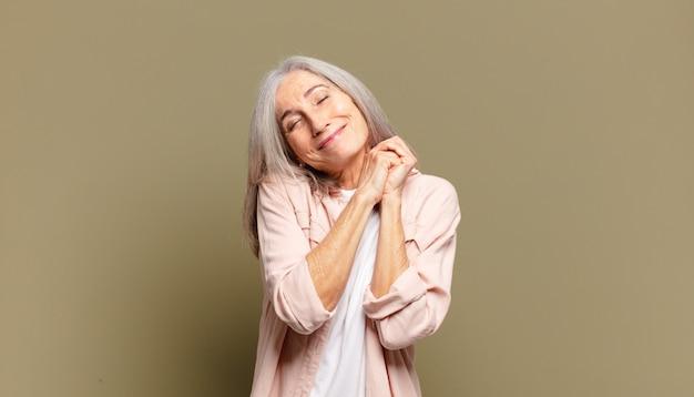 Starsza kobieta czuje się zakochana i wygląda uroczo, uroczo i szczęśliwie, uśmiechając się romantycznie z rękami przy twarzy