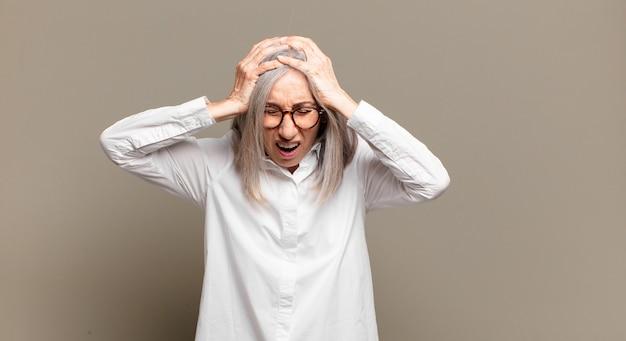 Starsza kobieta czuje się zestresowana i sfrustrowana, podnosi ręce do głowy, czuje się zmęczona, nieszczęśliwa i ma migrenę