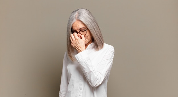 Starsza kobieta czuje się zestresowana, nieszczęśliwa i sfrustrowana, dotyka czoła i cierpi na migrenę lub silny ból głowy