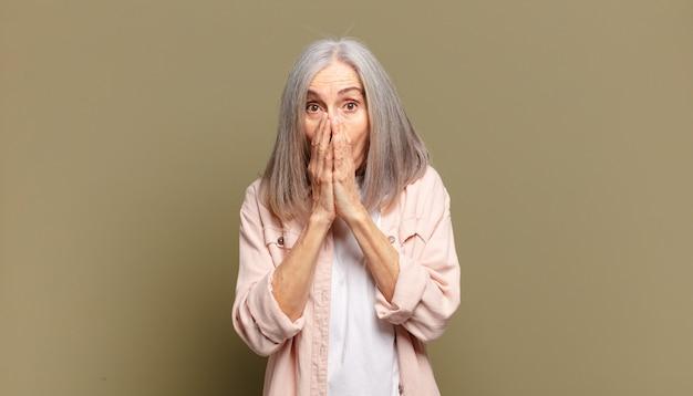 Starsza kobieta czuje się zmartwiona, zdenerwowana i przestraszona, zakrywa usta rękami, wygląda na zaniepokojoną i popsuła