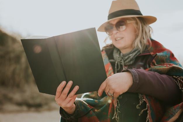 Starsza kobieta czyta książkę jako hobby