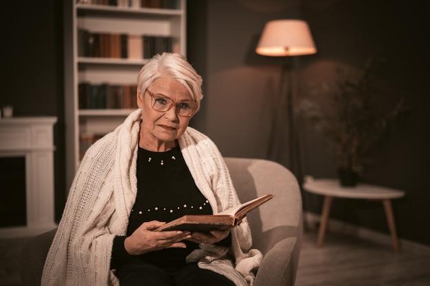 Starsza kobieta czyta starą książkę siedzi na krześle.
