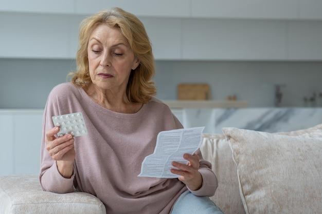 Starsza kobieta czyta w domu instrukcje dotyczące tabletek