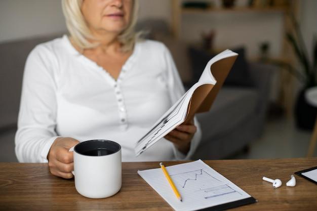 Starsza kobieta czytająca książkę na następne zajęcia