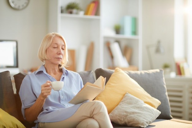 Starsza kobieta, czytanie książki w domu