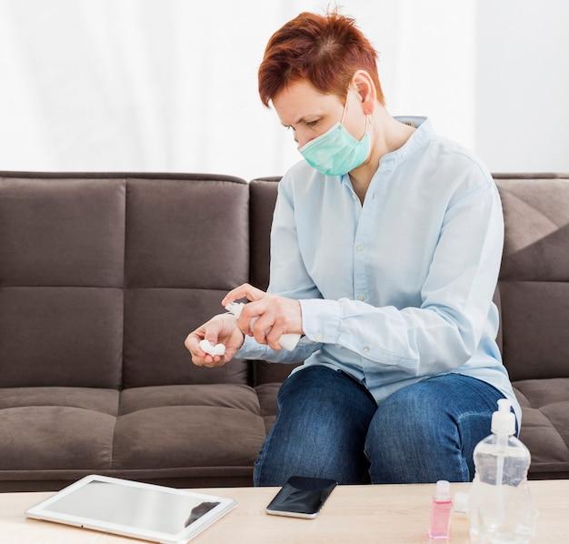 Starsza kobieta dezynfekująca swoje urządzenia w domu
