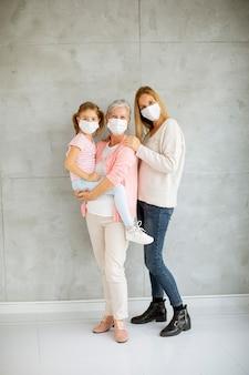Starsza kobieta, dorosła kobieta i śliczna mała dziewczynka, trzy pokolenia z ochronnymi maseczkami na twarz w domu