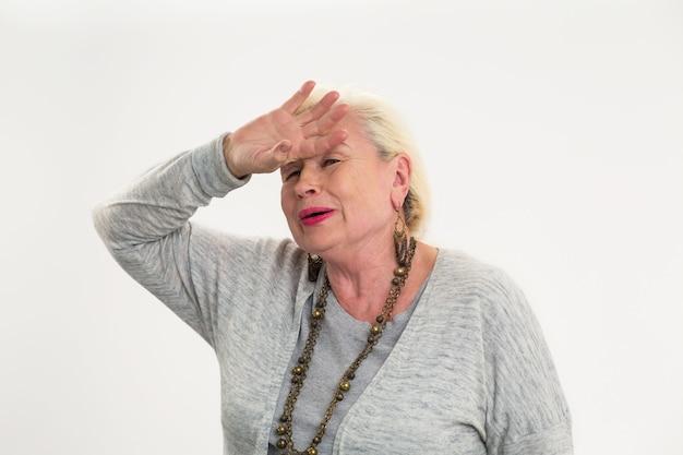 Starsza kobieta dotyka jej czoła. zmęczona pani na białym tle. silny pulsujący ból głowy.