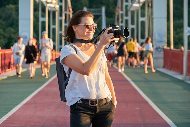 Starsza kobieta fotografowanie aparatem. kobieta dziennikarka fotograficzna, blogerka podróżnicza, kobieta w średnim wieku jako hobby