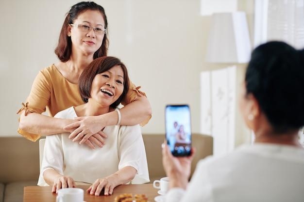 Starsza kobieta fotografuje szczęśliwe przytulanie starszych koleżanek siedzących przy stole