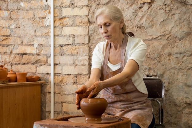 Starsza kobieta garncarka rzeźbi gliniany garnek rzeźbiarz pracuje z gliną na kole garncarskim i przy stole