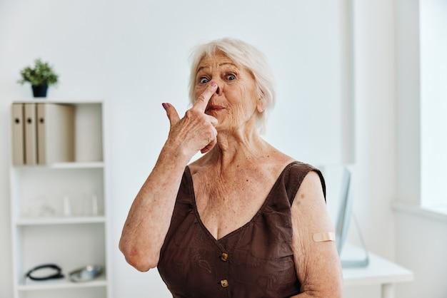 Starsza kobieta gips na ramieniu paszport szczepionkowy covid