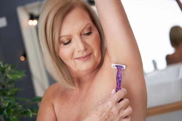Starsza kobieta goląca pachy w łazience