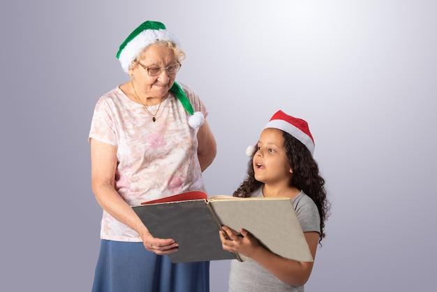 Starsza kobieta i dziecko w kapeluszu boże narodzenie czyta książkę na szaro