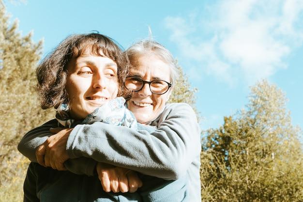 Starsza kobieta i jej córka uśmiechają się i bawią w lesie podczas szczęśliwego dnia matki mother