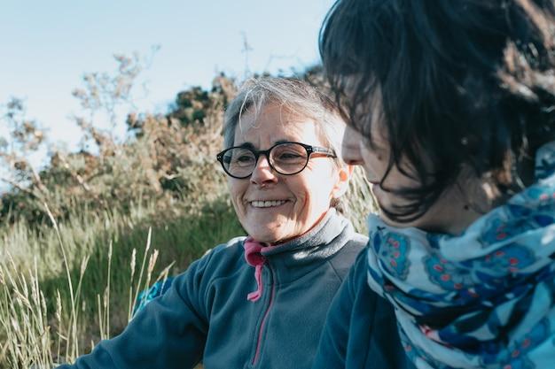 Starsza kobieta i jej córka uśmiechając się i bawiąc się na łonie natury w słoneczny dzień. szczęśliwego dnia matki
