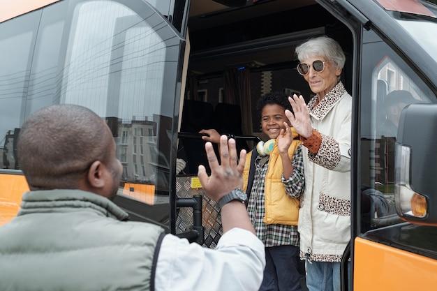 Starsza kobieta i jej wnuk macha rękami do młodego afrykanina