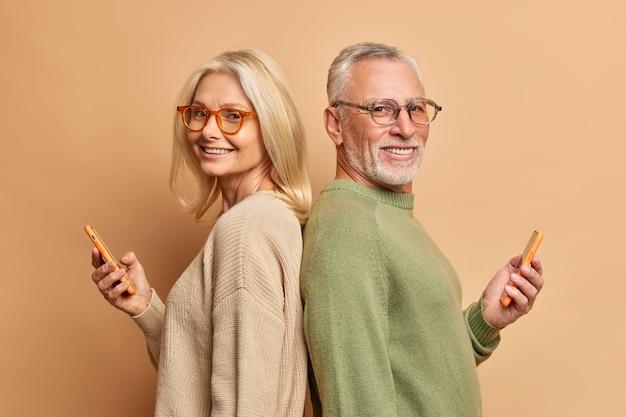 Starsza kobieta i mężczyzna stoją plecami do siebie, używają nowoczesnych telefonów komórkowych, stoją plecami do siebie, noszą okulary i swobodne swetry odizolowane na brązowej ścianie