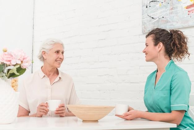 Starsza kobieta i żeńska pielęgniarka ma kawę wpólnie