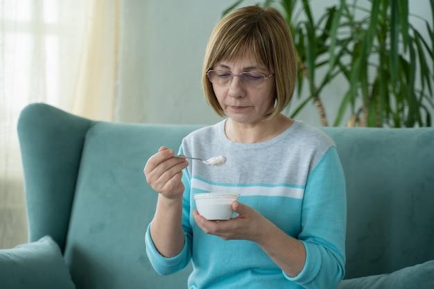 Starsza kobieta je jogurt siedząc na kanapie w domu