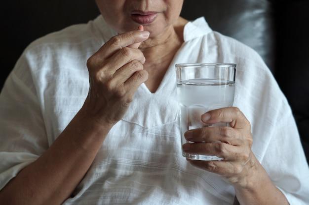 Starsza kobieta je lekarstwo iz pigułkami i szkłem woda w domu
