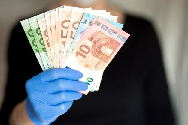 Starsza kobieta jest ubranym maskę trzyma gotówkowych euro banknoty w ręce w rękawiczkach. selektywne ustawianie ostrości. niebezpieczeństwo korzystania z gotówki