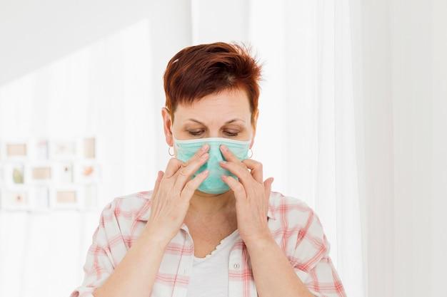Starsza kobieta jest ubranym medyczną maskę podczas gdy w domu